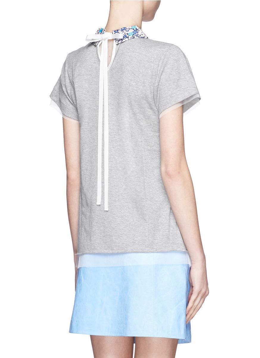 背面更以系绳取代常见的钮扣设计更见心思,衣领及衣摆的薄纱拼贴则